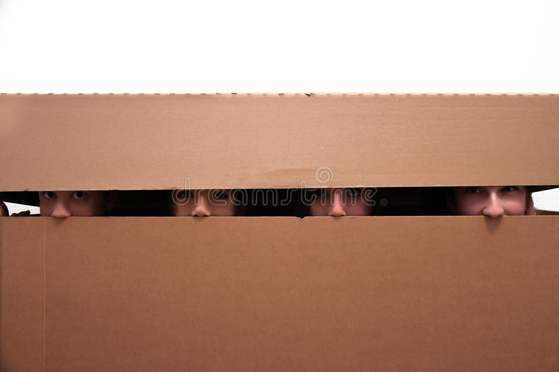 Teens hidden in moving box. Four teenager friends hidden in an empty moving box stock photography