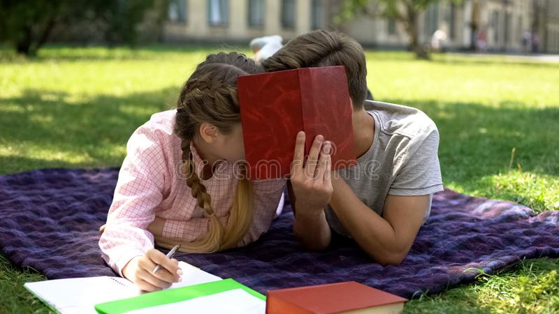 Teens hiding behind book and kissing, lying on plaid in park, first relations stock image