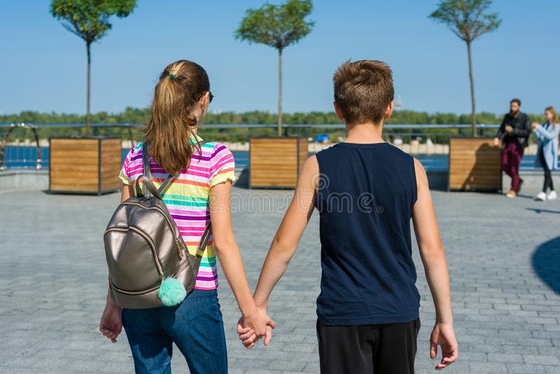 Teens holding hands rear view. Friendship, first love. stock photography