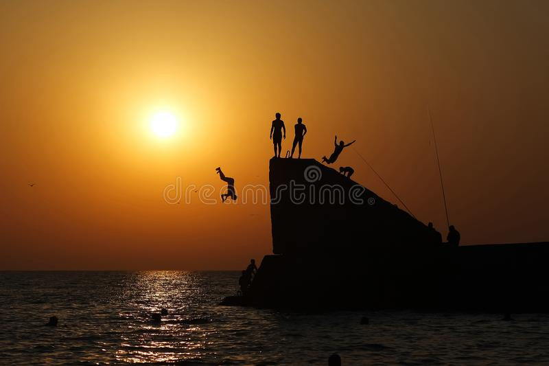 Teens jump from the pier into the sea. royalty free stock images