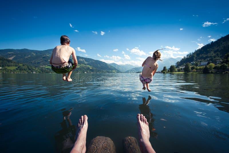 Teens jumping into lake stock image