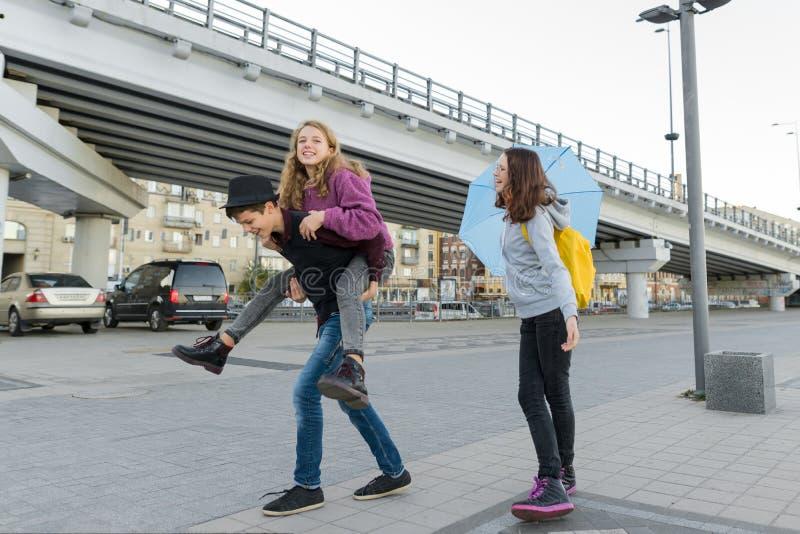 Teens Junge und zwei Mädchen reden und Spaß im Freien haben lizenzfreies stockbild