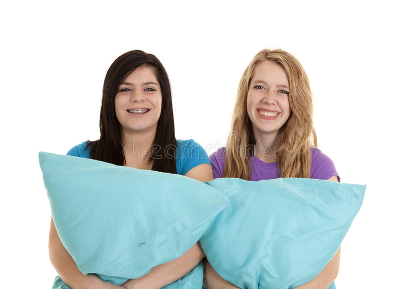 Teens pillows. Two teen girls holding on to their pillows smiling royalty free stock photos