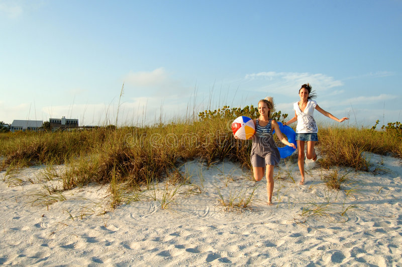 Teens running to the beach stock images