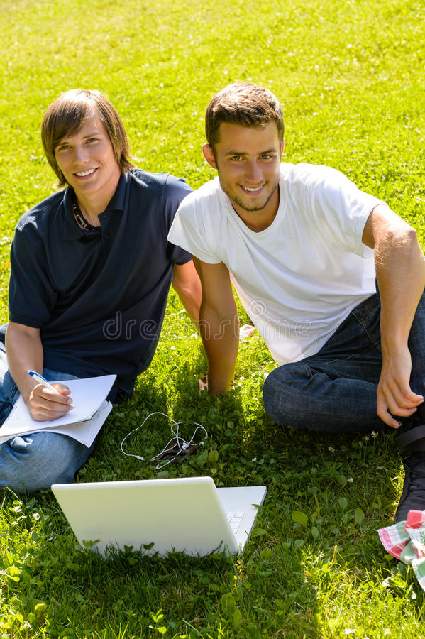 Teens sitting in park with laptop students stock images