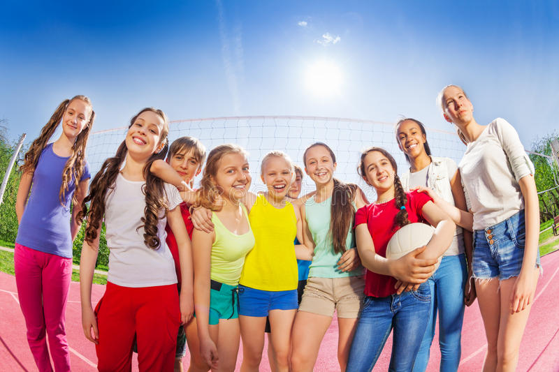 Teens stand in front of volleyball net, hold ball royalty free stock photos