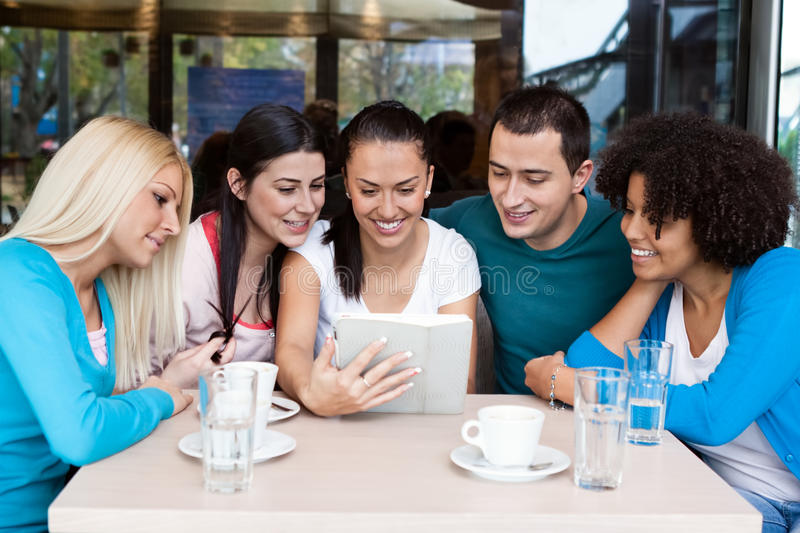 Teens using their digital tablet in a cafe royalty free stock photos