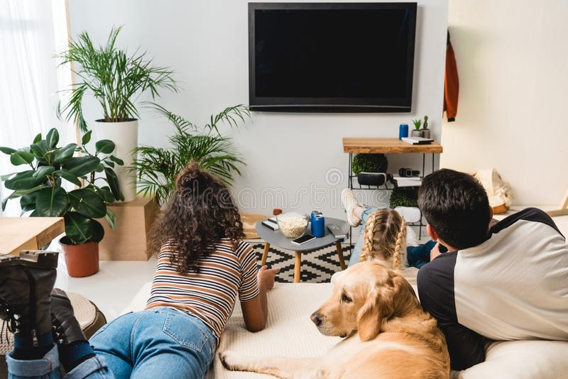 Teens watching tv and lying on bed. With dog royalty free stock photos