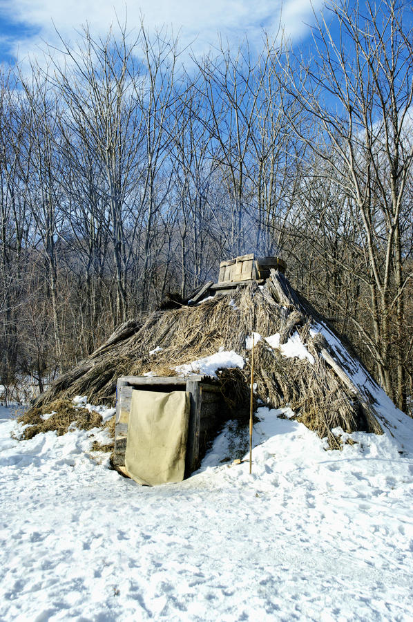 Teepee. In winter Against wood with a fire burning inside royalty free stock image