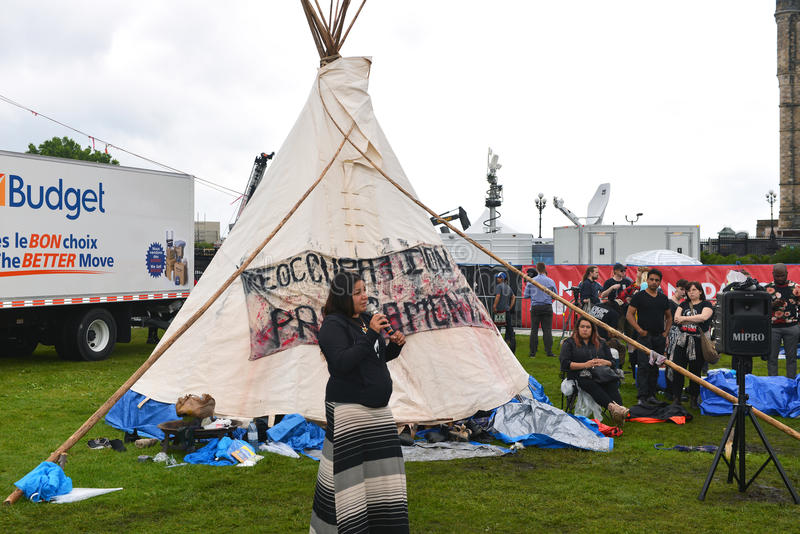 Teepee on Parliament Hill for Canada Day celebration. Ottawa, Canada - June 30, 2017: Candace Day Neveau addresses the crowd gathered around the controversial stock image
