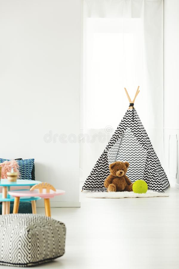 Teepee with teddy bear. Patterned teepee with a teddy bear and yellow ball inside set in white kid`s room interior stock photos