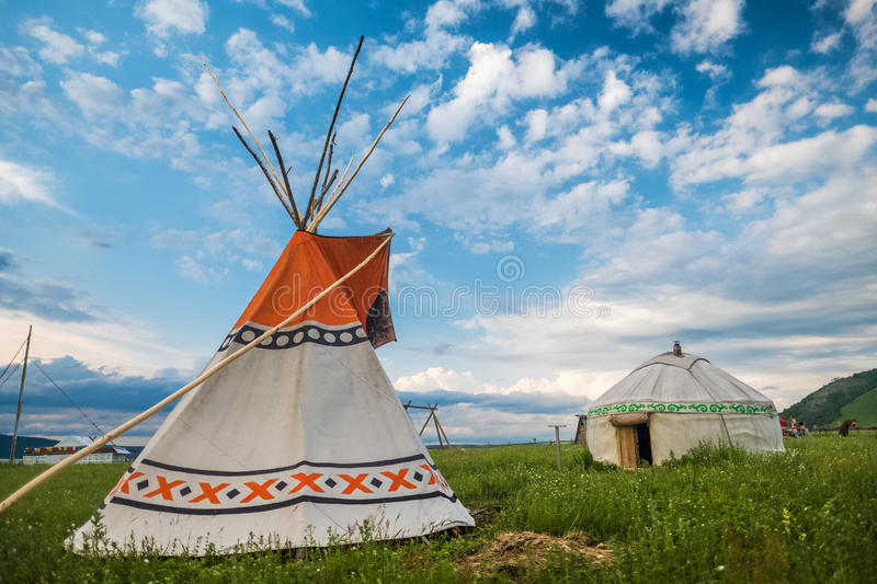 Teepee and yurt. Set on the green meadow with blue sky on the background royalty free stock images