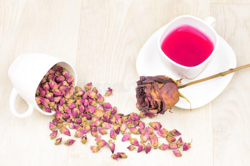 Teerosen zerstreut, heißer Tee und getrocknete rosafarbene Blume auf hölzernem Vorsprung stockfotos