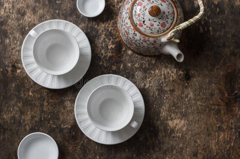 Teesatz auf einem Holztisch, Draufsicht Teekanne, leere weiße Teeschale auf einem braunen Hintergrund, Draufsicht stockfoto