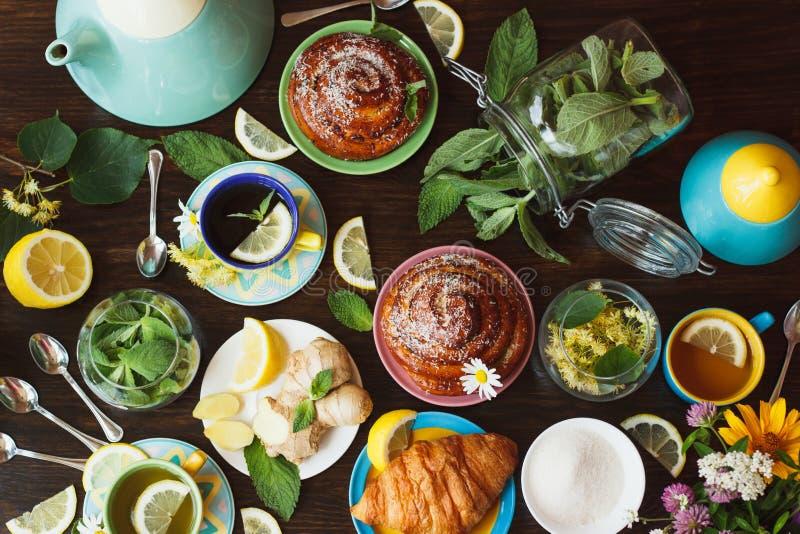 Teesatz: Grüner Tee mit Zitrone und tadellose und verschiedene Backwaren mit einer knusperigen Kruste auf dem hölzernen Hintergru lizenzfreies stockbild