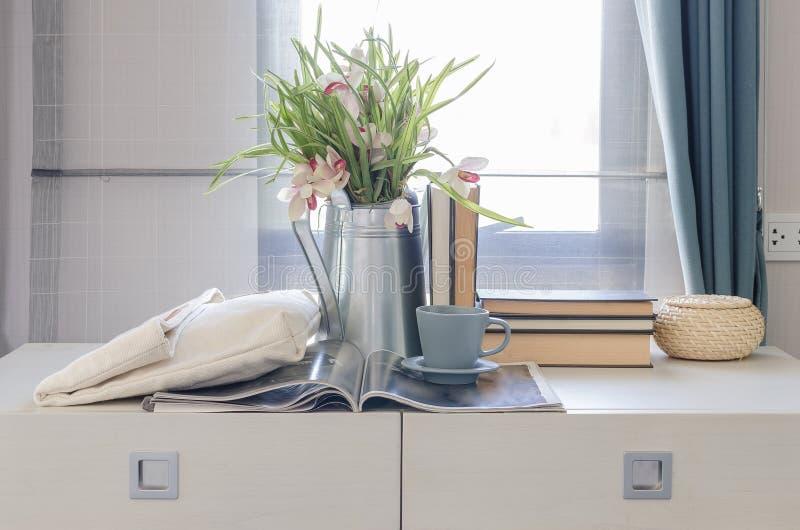 Teeschale auf Buch mit Vase der Blume auf weißem Schreibtisch lizenzfreies stockbild