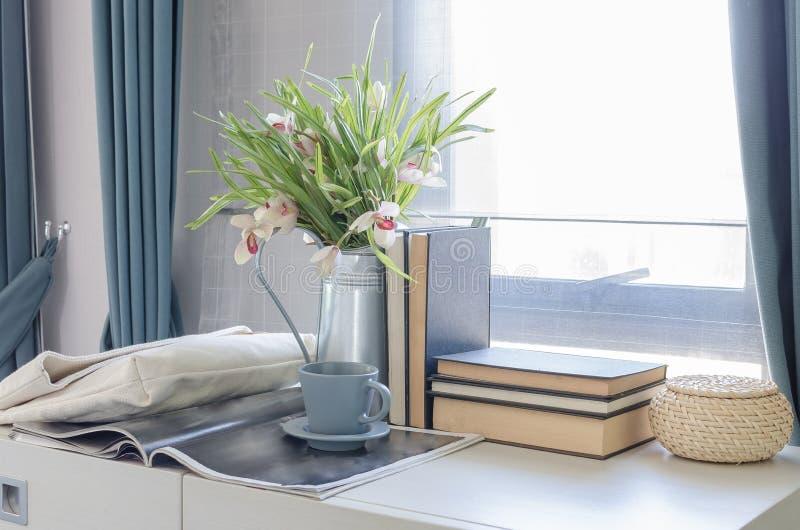 Teeschale auf Buch mit Vase der Blume auf weißem Schreibtisch stockbild