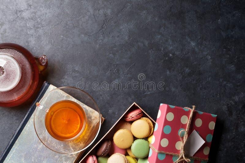 Teeschale, Teekanne und Makronen stockfotografie