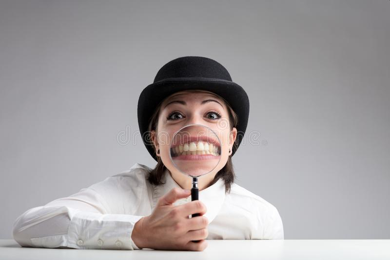 Teeth behind a magnifier and a funny face stock photography