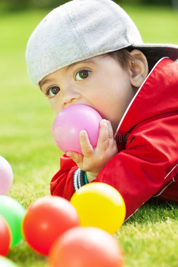 When teeth are growing. Adorable kid playing and biting ball stock images