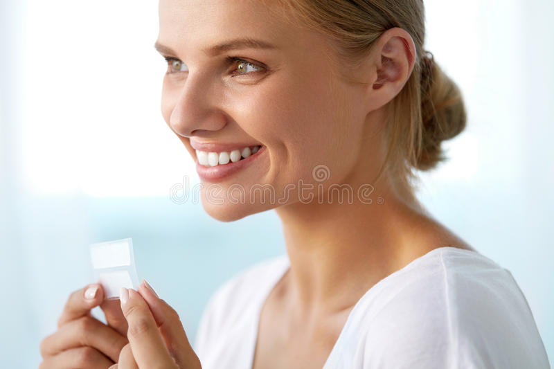 Teeth Whitening. Beautiful Smiling Woman Holding Whitening Strip. Teeth Whitening. Closeup Portrait Of Beautiful Happy Smiling Young Woman With Perfect Smile stock photo