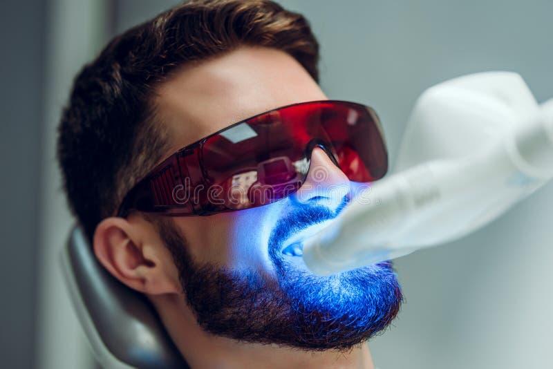 Teeth whitening. Man having teeth whitened by dental UV laser whitening device. Teeth whitening machine,eyes protected with. Teeth whitening. Man having teeth royalty free stock images