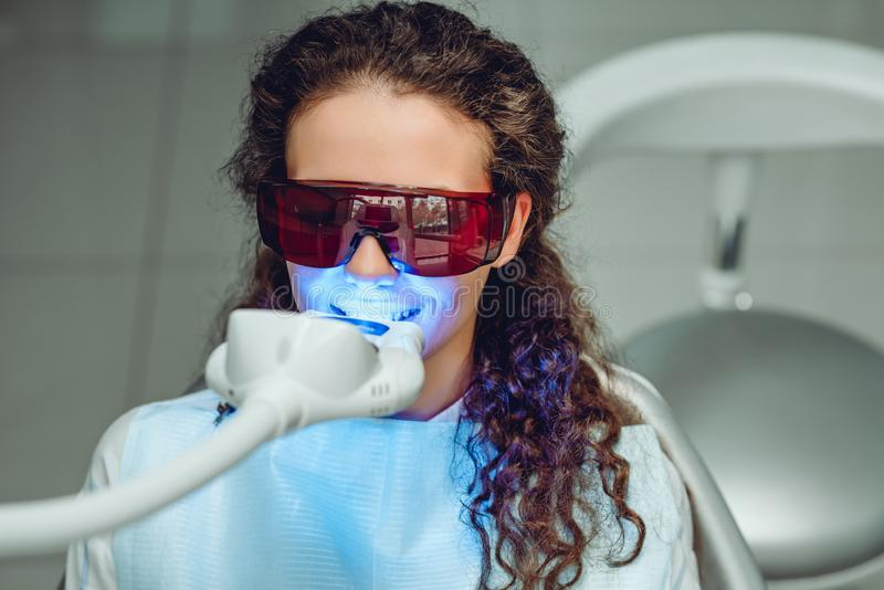 Teeth whitening for woman. Bleaching of the teeth at dentist clinic. Front view royalty free stock photography