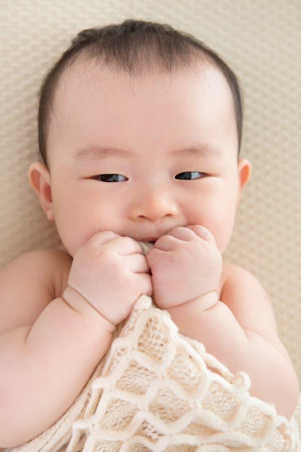 Teething Asian baby girl stock photo