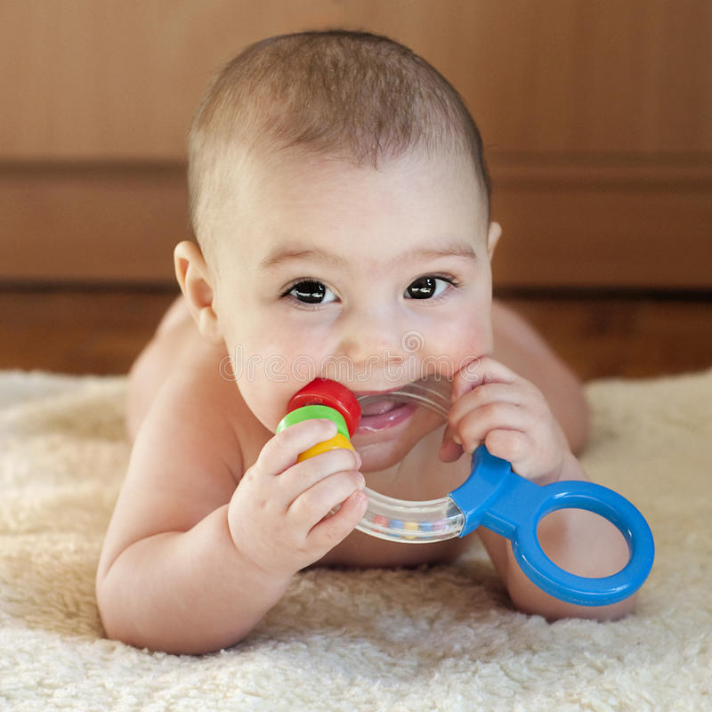 Teething baby. Portrait of a cute 6 month old baby, boy or girl, playing with a teething toy stock photography