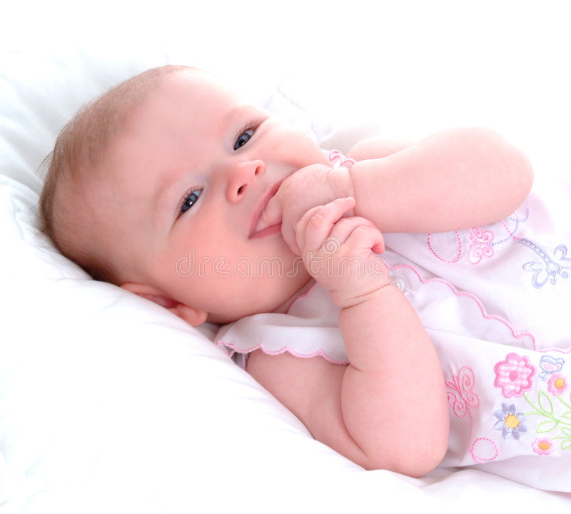 Teething Baby. Teething aby girl lying in front of white background on blanket stock photos