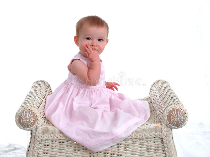 Teething Baby Girl. On wicker bench, with two fingers in her mouth royalty free stock photography