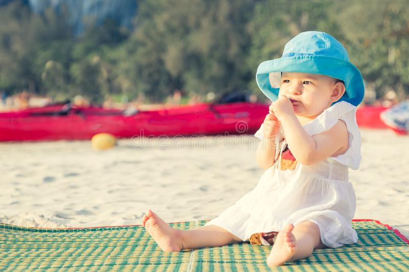 Teething in 8 mounth. Baby girl sitting on the beach and chews a teether. In blue hat and white dress on bamboo mat stock photography