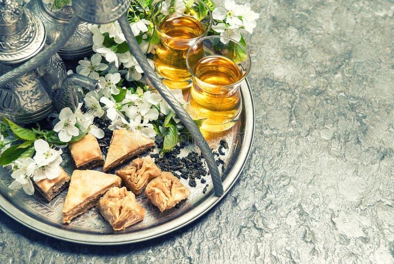 Teexponeringsglas och kruka, traditionell kakabaklava Islamisk holida royaltyfri bild
