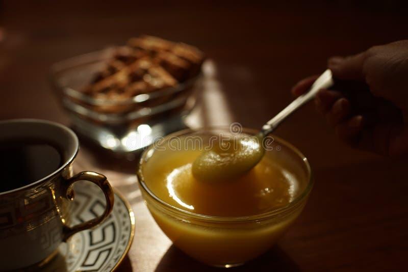 Teezeit Honig in einer Glasschüssel mit Löffellöffel, eine Tasse Tee auf einer Untertasse, Kekse in einer Vase auf dem Tisch lizenzfreie stockfotos