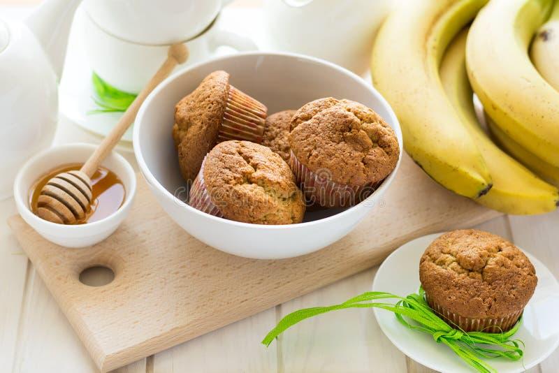 Teezeit: selbst gemachte Bananenmuffins, Honig, Bananen und Teeeinstellungen lizenzfreies stockbild