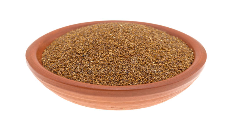 Teff grain filling a small bowl on a white background. A small bowl of teff grain isolated on a white background stock photo
