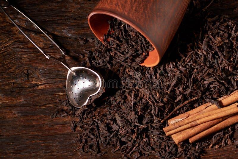 Tefilter med en kopp och ett svart te på trätabellen på mörk bakgrund Selektivt fokusera fotografering för bildbyråer