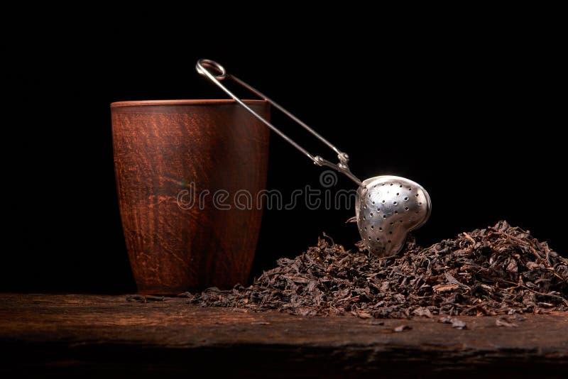 Tefilter med en kopp och ett svart te på trätabellen på mörk bakgrund Selektivt fokusera arkivfoto