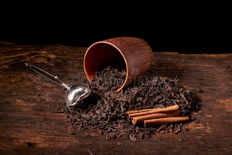 Tefilter med en kopp och ett svart te på trätabellen på mörk bakgrund Selektivt fokusera royaltyfri bild
