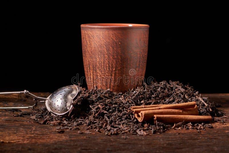 Tefilter med en kopp och ett svart te på trätabellen på mörk bakgrund Selektivt fokusera royaltyfria bilder