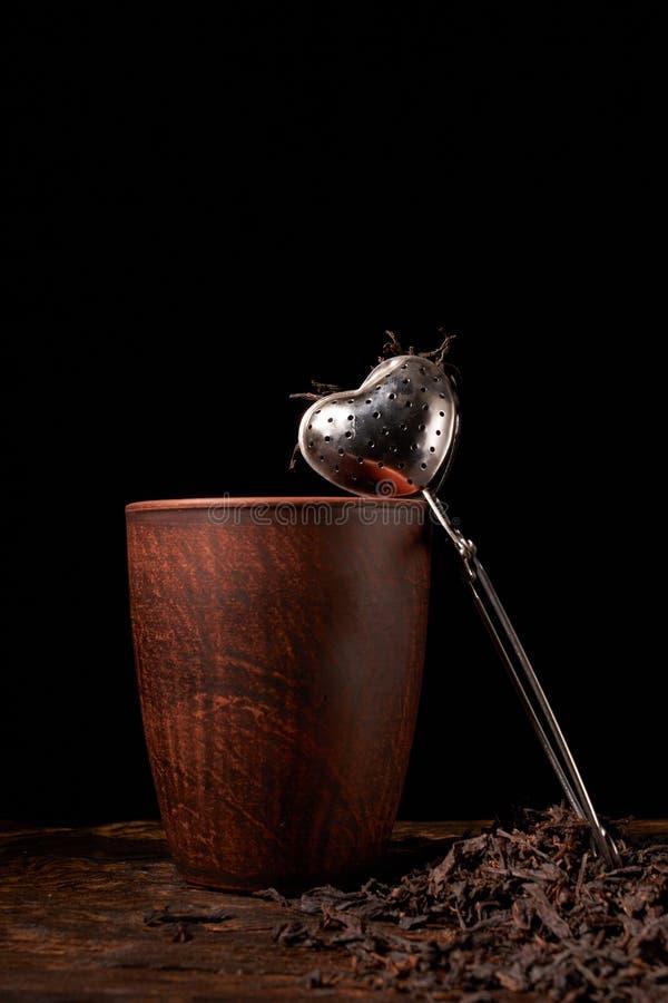 Tefilter med en kopp och ett svart te på trätabellen på mörk bakgrund Selektivt fokusera arkivbild