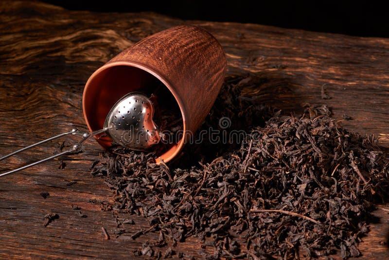 Tefilter med en kopp och ett svart te på trätabellen på mörk bakgrund Selektivt fokusera royaltyfria foton