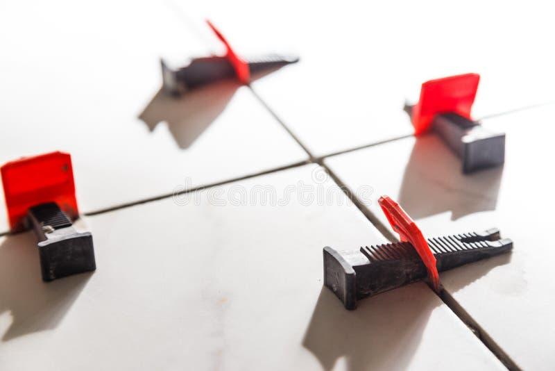 Tegel nivellerend systeem met plastic klemmen en wiggen stock afbeelding