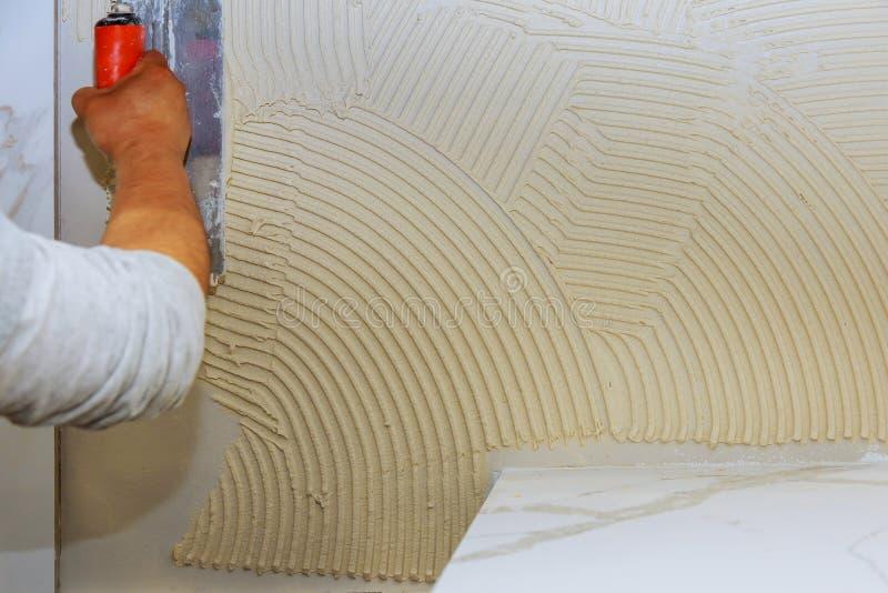 Tegelplatta som förläggas över mastix i hem- renovering royaltyfri bild
