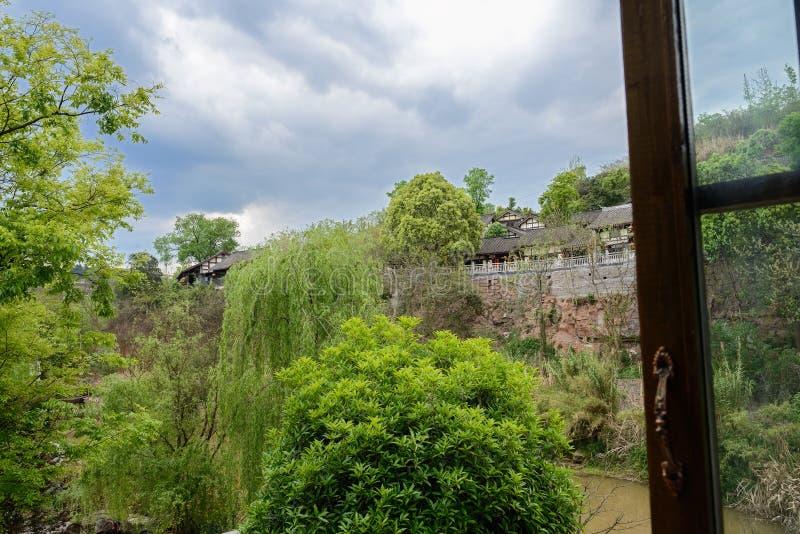 Tegelplatta-taklade byggnader på flodstrandklippan i den aftern molniga våren arkivfoto