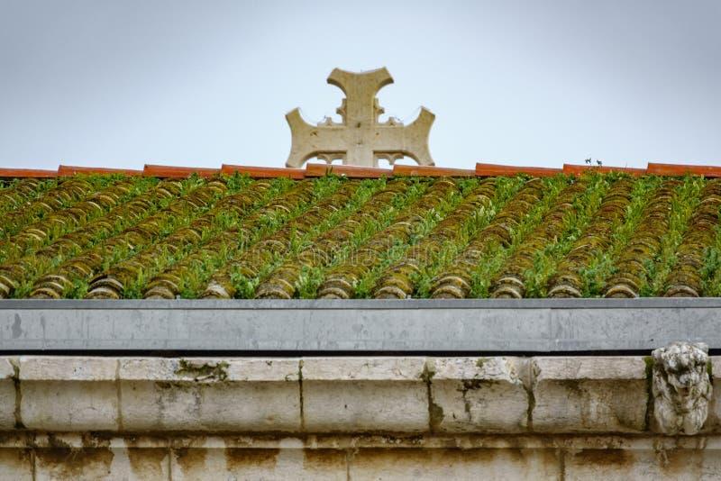 Tegelplattatak som täckas med gräs och det suddiga korset arkivbild