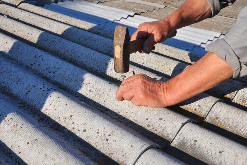 Tegelplattor för tak för farlig asbest för reparation gamla Arbetaren installerar asbesttaksinglar - closeup på händer royaltyfri bild