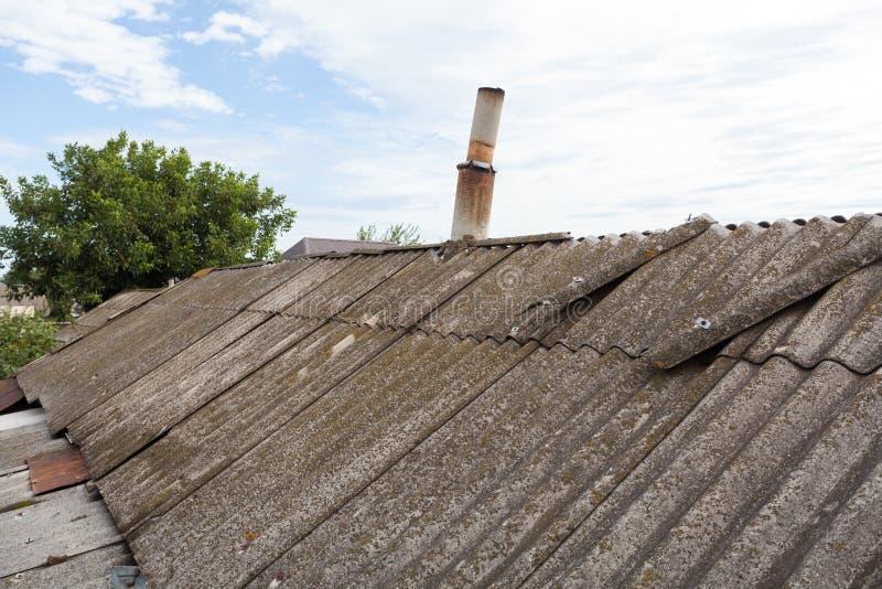 Tegels van het asbest de oude gevaarlijke dak stock afbeelding