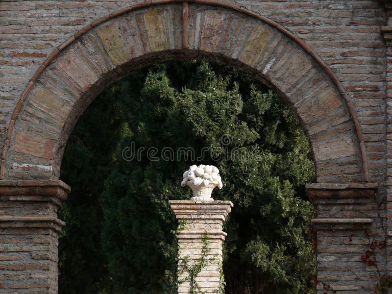 Tegelstenbågen och vit marmorerar skulptur arkivfoton