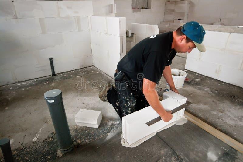 tegelstenbyggmästare som lägger inomhus arkivbild
